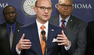 FILE - In this May 16, 2017, file photo, Oklahoma state Rep. Scott Inman, D-Oklahoma City, surrounded by members of the Democratic caucus, answers a question during a news conference in Oklahoma City. Inman on Wednesday, Oct. 25, 2017, announced he is dropping out of the governor's race and plans to resign from his House seat early next year, citing the stress of the campaign on his personal life. (AP Photo/Sue Ogrocki, File)