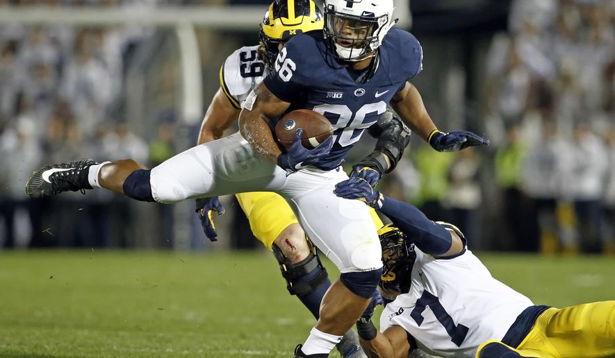 FILE - In this Saturday, Oct. 21, 2017, file photo, Penn State's Saquon Barkley (26) makes a move on Michigan's Khaleke Hudson (7) during the first half of an NCAA college football game in State College, Pa. Barkley has run roughshod over Big Ten defenses this year, including Michigan's vaunted defense last Saturday. Now he'll face Ohio State at home this week. What do the Buckeyes plan to do to stop him?  (AP Photo/Chris Knight, File)