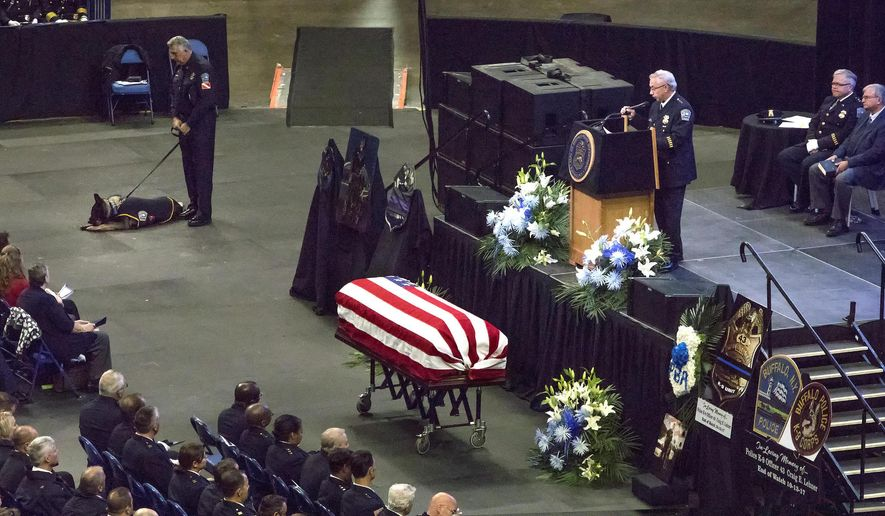 In this photo provided by WBFO News, the casket of Buffalo Police Officer Craig Lehner is positioned in front of the state at Key Bank Center, during Lehner's funeral in Buffalo, N.Y., Wednesday, Oct. 25, 2017. Lehner was killed in a training dive accident in the Niagara River on Oct. 13. At top left is his canine partner Shield. (Eileen Koteras Elibol/WBFO News via AP)