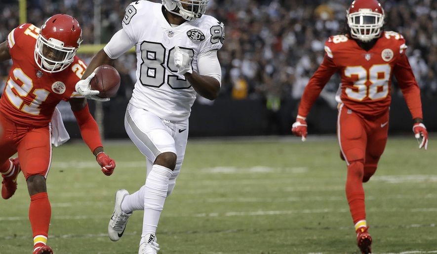 FILE - In this Oct. 19, 2017, file photo, Oakland Raiders wide receiver Amari Cooper (89) runs past Kansas City Chiefs cornerback Eric Murray (21) and defensive back Ron Parker (38) to score a touchdown during the first half of an NFL football game in Oakland, Calif. By moving Cooper around, the Raiders were finally able to get their star receiver going last week. (AP Photo/Marcio Jose Sanchez, File)