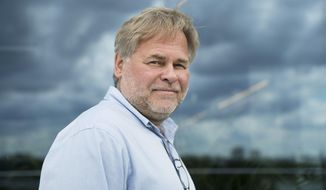 FILE - In this July 1, 2017, file photo, Eugene Kaspersky, Russian antivirus programs developer and chief executive of Russia's Kaspersky Lab, poses for a photo on a balcony at his company's headquarters in Moscow, Russia. The founder of Russian anti-virus firm Kaspersky tells The Associated Press his company did upload classified U.S. documents a couple of years ago, only to delete them immediately after realizing what had happened. Kaspersky's acknowledgement is the first on-the-record confirmation of an incident described earlier this month in three U.S. newspapers.(AP Photo/Pavel Golovkin, File)