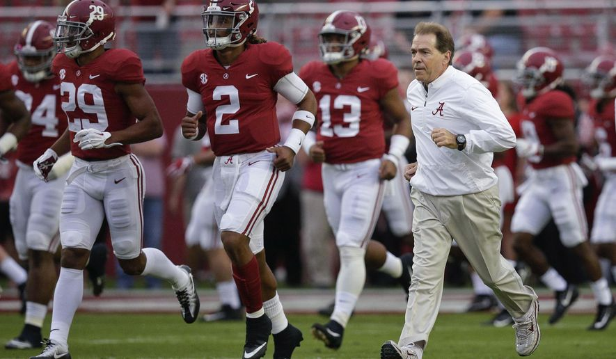 FILE - In this Saturday, Oct. 14, 2017, file photo, Alabama coach Nick Saban and quarterback Jalen Hurts (2) runs onto the field before the team's NCAA college football game against Arkansas in Tuscaloosa, Ala. No. 1 Alabama and No. 3 Georgia are on track to give the SEC two undefeated teams in the championship game for the first time since 2009.  (AP Photo/Brynn Anderson, File)