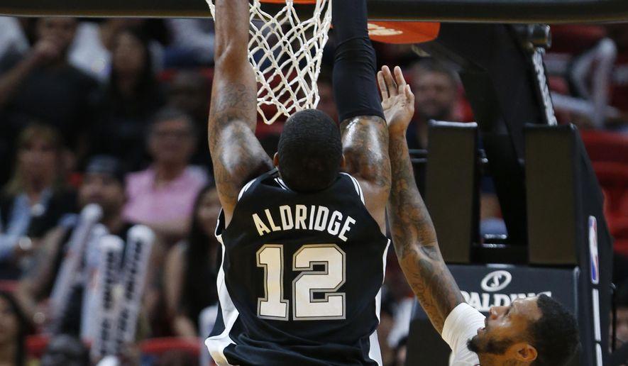 San Antonio Spurs forward LaMarcus Aldridge (12) dunks the ball against Miami Heat forward James Johnson (16) during the first half of an NBA basketball game, Wednesday, Oct. 25, 2017, in Miami. (AP Photo/Wilfredo Lee)