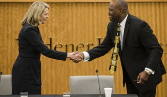 Pennsylvania Supreme Court candidates Republican Sallie Mundy, a justice on the state Supreme Court, left, and Democratic candidate Dwayne Woodruff, a common pleas court judge in Allegheny County shake hands at the end of a debate at the Widener University Commonwealth Law School in Harrisburg, Pa., Wednesday, Oct. 25, 2017. (AP Photo/Matt Rourke)