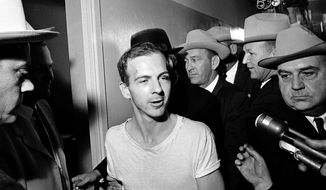 In this Nov. 23, 1963, file photo, surrounded by detectives, Lee Harvey Oswald talks to the media as he is led down a corridor of the Dallas police station for another round of questioning in connection with the assassination of U.S. President John F. Kennedy. (AP Photo)