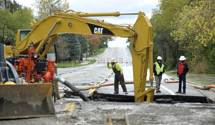 Great Lakes Water Authority (GLWA) employees and sub-contractors dig up part of 14 Mile Rd. just east of Verona St. in West Bloomfield, Mich., Tuesday, Oct. 24, 2017, as they repair a transmission water main break affecting at least 11 Western Oakland County communities and more than 250,000 residents and businesses with a boil-water alert until possibly Friday afternoon. (Todd McInturf/The Detroit News via AP)