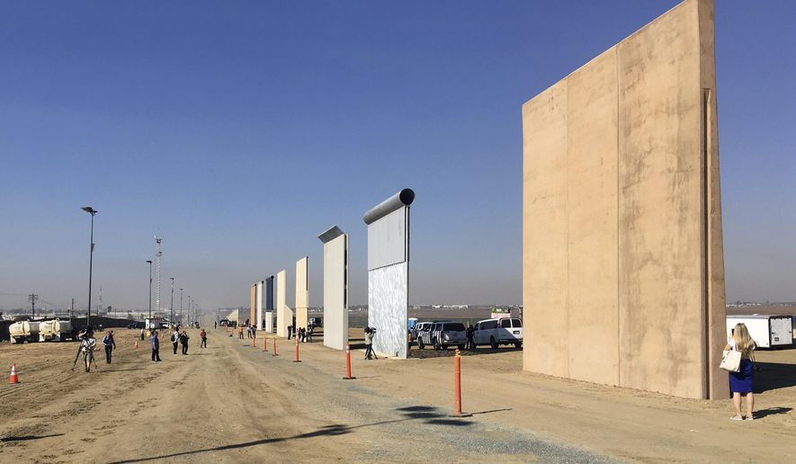 People look at prototypes of a border wall Thursday, Oct. 26, 2017, in San Diego. Contractors have completed eight prototypes of President Donald Trump's proposed border wall with Mexico, triggering a period of rigorous testing to determine if they can repel sledgehammers, torches, pickaxes and battery-operated tools. (AP Photo/Elliott Spagat) ** FILE **