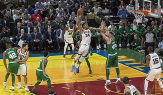 Milwaukee Bucks' Giannis Antetokounmpo leaps for a dunk but is fouled by Boston Celtics' Aron Baynes during the first half of an NBA basketball game Thursday, Oct. 26, 2017, in Milwaukee. (AP Photo/Tom Lynn)