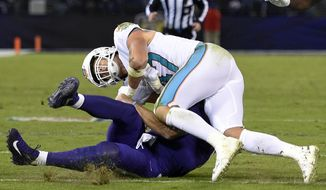 Miami Dolphins middle linebacker Kiko Alonso, top, collides with Baltimore Ravens quarterback Joe Flacco as Flacco slides on the field after rushing the ball in the first half of an NFL football game, Thursday, Oct. 26, 2017, in Baltimore. (AP Photo/Nick Wass)