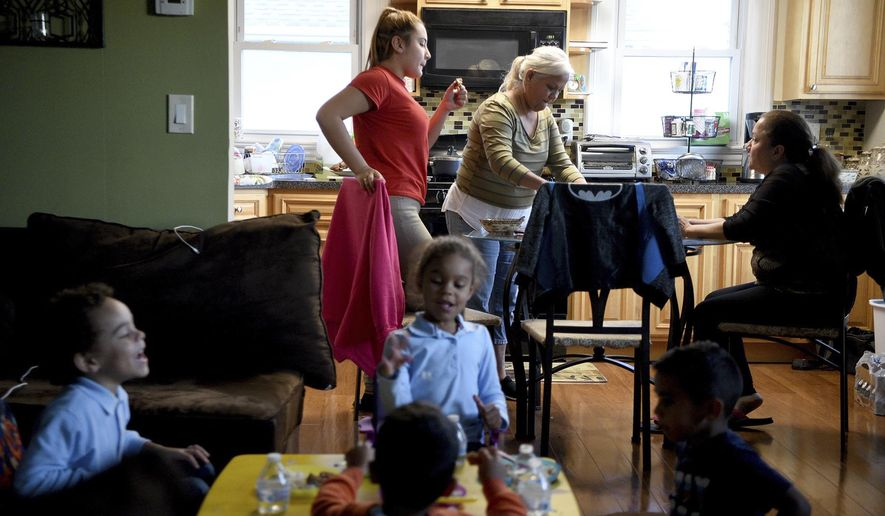 In a Oct. 17, 2017 photo, Norma Navarro Ortiz, center rear, of Salinas, Puerto Rico, stands at a kitchen table across from her sister Arianette Fuentes, right, as Ortiz's two grandchildren play with her sister's young children, in Hackensack, N.J. Residents of Puerto Rico and the U.S. Virgin Islands have wound up in New Jersey, the state with the third largest Puerto Rican population in the country after Florida and New York, as part of a continuing exodus from territories devastated by consecutive hurricanes. Ortiz has been gathering and sending supplies that were unavailable in Puerto Rico, including batteries, generators, insect repellent, nutrition drinks, solar-powered lamps and other necessities. (Amy Newman/The Record via AP)