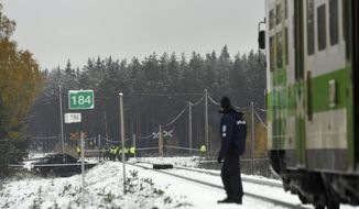 Rescue, military personnel and a policeman gather at the railroad crossing, where several people were killed in a crash between a train, right, and a military truck, left, by the track, in southern Finland Thursday Oct. 26, 2017.  Finnish media say several people have been killed in a train crash in the southern part of Finland. (Lehtikuva via AP)