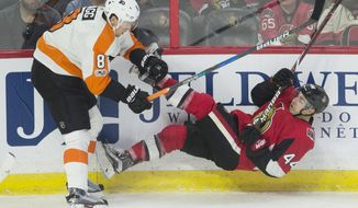 Philadelphia Flyers defenseman Robert Hagg, left, collides with Ottawa Senators center Jean-Gabriel Pageau along the boards during the first period of an NHL hockey game, Thursday, Oct. 26, 2017 in Ottawa, Ontario. (Adrian Wyld/The Canadian Press via AP)