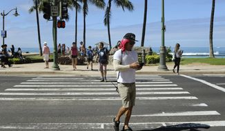 In this Wednesday, Oct. 25, 2017, photo, a man uses his cellphone while crossing a street in Honolulu. A new Honolulu ordinance allows police officers to issue tickets to pedestrians caught looking at a cellphone or electronic device while crossing a city street. (AP Photo/Caleb Jones)