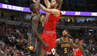 Chicago Bulls center Robin Lopez, right, shoots over Atlanta Hawks center Dewayne Dedmon during the first half of an NBA basketball game Thursday, Oct. 26, 2017, in Chicago. (AP Photo/Charles Rex Arbogast)
