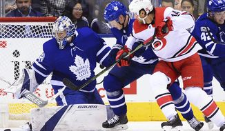 Toronto Maple Leafs goalie Frederik Andersen (31) makes a save as Maple Leafs defenseman Andreas Borgman (55) and Carolina Hurricanes right wing Justin Williams (14) battle during the second period of an NHL hockey game, Thursday, Oct. 26, 2017 in Toronto. (Frank Gunn/The Canadian Press via AP)