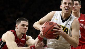 FILE - In this March 15, 2017, file photo, Iowa guard Jordan Bohannon, right, drives past South Dakota guard Matt Mooney, left, during the first half of a first-round game in the NIT college basketball tournament in Iowa City, Iowa.  Iowa lost its best player from a team that failed to reach the NCAA Tournament. Yet the feeling in Iowa City is that the Hawkeyes could be on the verge of returning to prominence in the Big Ten. (AP Photo/Charlie Neibergall, File)