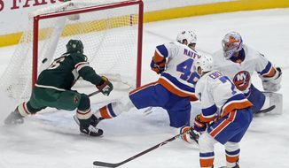 Minnesota Wild's Jason Zucker, left, scores on New York Islanders goalie Thomas Greiss, right, of Germany during the first period of an NHL hockey game Thursday, Oct. 26, 2017, in St. Paul. Minn. (AP Photo/Jim Mone)