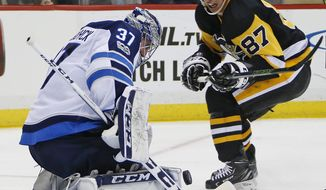 Winnipeg Jets goalie Connor Hellebuyck (37) stops a shot by Pittsburgh Penguins' Sidney Crosby (87) in the second period of an NHL hockey game in Pittsburgh, Thursday, Oct. 26, 2017. (AP Photo/Gene J. Puskar)