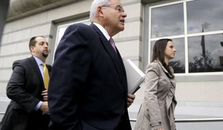 U.S. Sen. Bob Menendez, center, arrives at the Martin Luther King, Jr., Federal Courthouse for his federal corruption trial, Thursday, Oct. 26, 2017, in Newark, N.J. (AP Photo/Julio Cortez)