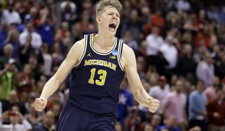 FILE - In this March 19, 2017, file photo, Michigan forward Moritz Wagner (13) celebrates a 73-69 win over Louisville in a second-round game in the men's NCAA college basketball tournament in Indianapolis. Michigan will ask Wagner to do a little bit of everything as the Wolverines try for another successful season. (AP Photo/Michael Conroy, File)