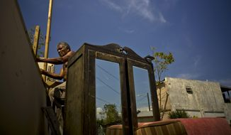 FILE - In this Oct. 9, 2017 file photo, Efrain Diaz Figueroa attempts to repair the roof of his sister's home destroyed by Hurricane Maria in San Juan, Puerto Rico. Figueroa, 70, was visiting his sister when the Hurricane Maria hit the area, and also lost his home in the Arroyo area. (AP Photo/Ramon Espinosa, File)