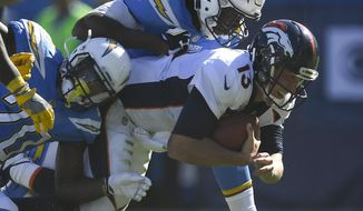"FILE - In this Oct. 22, 2017, file photo, Denver Broncos quarterback Trevor Siemian, right, is tackled by Los Angeles Chargers defensive end Chris McCain, top and defensive back Desmond King during the first half of an NFL football game, in Carson, Calif. The Denver Broncos are red-faced over their poor play and their quarterback has a black and blue nose courtesy of his latest trouncing. It's only a bruise, Siemian said, but ""I probably should have broken it. I deserve it the way I played.""(AP Photo/Mark J. Terrill, File)"