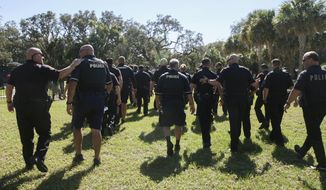 """In this Wednesday, Oct. 25, 2017 photo, members of the Tampa Police Department leave Giddens Park after a roll call and press conference in the Seminole Heights neighborhood in Tampa, Fla. The mayor of the Florida told police officers looking for a suspect in three fatal and apparently random shootings in the neighborhood to hunt him down and """"bring his head to me.""""  (Gabriella Angotti-Jones/Tampa Bay Times via AP)"""