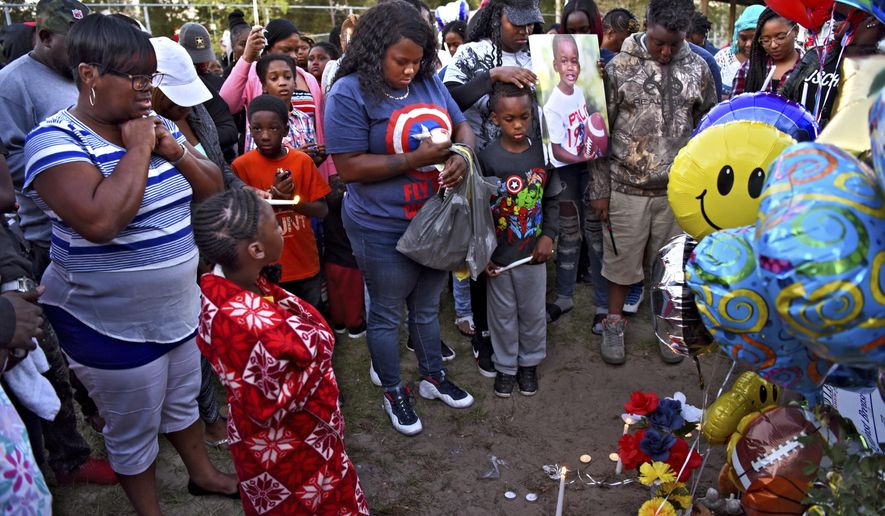 "As friends and family gather around the balloons, candles and toys left atop the tank where Amari Harley, 3, was found, his mother Jasmine Bates places her hand on her six-year-old son Jamaris' head as she clutches a photo of Amari during a vigil in Bruce Park, Wednesday, Oct. 25, 2017, in Jacksonville, Fla. Jacksonville Mayor Lenny Curry said the ""city is in mourning"" over the death of Amari Harley, who went missing during a family outing at Bruce Park on Sunday. His body was found in the tank hours later. (Bob Mack/The Florida Times-Union via AP)"