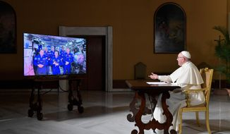 Pope Francis speaks to the crew aboard the International Space Station from the Vatican, Thursday, Oct. 26, 2017. Pope Francis' hookup Thursday will mark the second papal phone call to space: Pope Benedict XVI rang the space station in 2011, and peppered its residents with questions about the future of the planet and the environmental risks it faced. (L'Osservatore Romano/Pool Photo via AP)