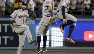 Houston Astros left fielder Marwin Gonzalez, from left, Carlos Correa and George Springer celebrate their win against the Los Angeles Dodgers during Game 2 of baseball's World Series Wednesday, Oct. 25, 2017, in Los Angeles. The Astros won 7-6 to tie the series at 1-1. (AP Photo/Matt Slocum)