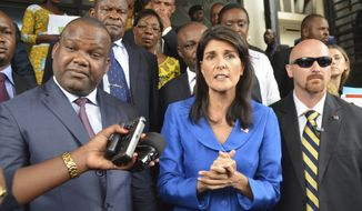 Nikki Haley, U.S. ambassador to the United Nations, centre, meets with President of Congo's Election commission, Corneil Nangaa, left, during a meeting in Kinshasa, Congo, Friday, Oct. 27, 2017. The U.S. ambassador to the United Nations says Congo will not have the help of the international community if elections are not held in 2018.  (AP Photo/John Bompengo)