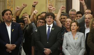 Catalan President Carles Puigdemont, center, Vice President Oriol Junqueras, left, and Carme Forcadell, the parliament president, sing the Catalan anthem inside the parliament after a vote on independence in Barcelona, Spain, Friday, Oct. 27, 2017. Catalonia's regional parliament has passed a motion saying they are establishing an independent Catalan Republic.(AP Photo/Manu Fernandez)