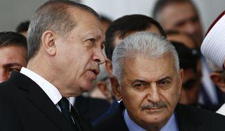 Turkey's President Recep Tayyip Erdogan, left, talks to Turkey's Prime Minister Binali Yildirim, right, as they attend the inauguration ceremony of the Melike Hatun mosque in Ankara, Turkey, Friday, Oct 27, 2017. (AP Photo/Burhan Ozbilici)