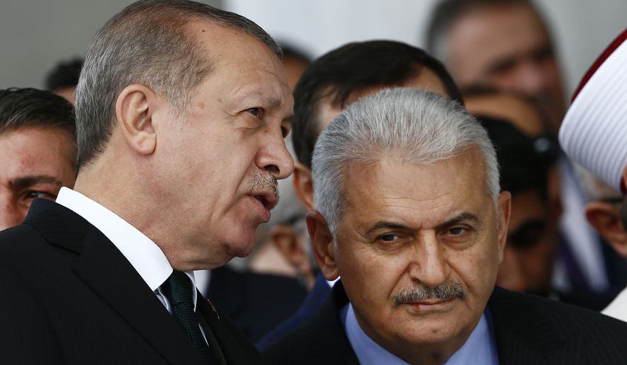 Turkey's President Recep Tayyip Erdogan, left, talks to Turkey's Prime Minister Binali Yildirim, right, as they attend the inauguration ceremony of the Melike Hatun mosque in Ankara, Turkey, Friday, Oct 27, 2017. (AP Photo/Burhan Ozbilici)