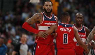 Washington Wizards forward Mike Scott (30) and Washington Wizards guard Tim Frazier (8) in the second half of an NBA basketball game Monday, Oct. 23, 2017, in Denver. The Wizards won 109-104. (AP Photo/David Zalubowski)