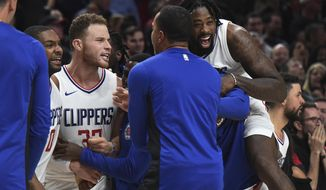Los Angeles Clippers forward Blake Griffin is mobbed by his teammates after hit the game winning shot during the fourth quarter of an NBA basketball game against the Portland Trail Blazers in Portland, Ore., Thursday, Oct. 26, 2017. The Clippers won 104-103. (AP Photo/Steve Dykes)