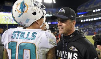 Baltimore Ravens head coach John Harbaugh, right, speaks with Miami Dolphins wide receiver Kenny Stills after an NFL football game, Thursday, Oct. 26, 2017, in Baltimore. Baltimore won 40-0. (AP Photo/Nick Wass)