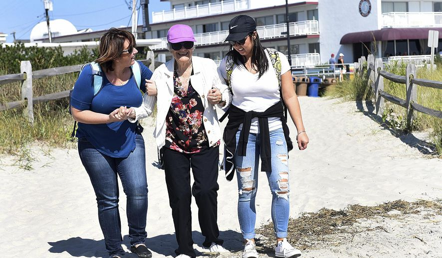 In this Thursday, Sept. 21, 2017 photo, Odette Swan, center, is helped onto the beach at Ocean City, N.J., by her granddaughter, Samantha Jonsson, left, and Pine Run nurse, Laura Watson. The trip was planned by Pine Run staff to help rekindle memories of dementia patients by taking them to and old familiar place from their past. (Art Gentile/The Intelligencer via AP)