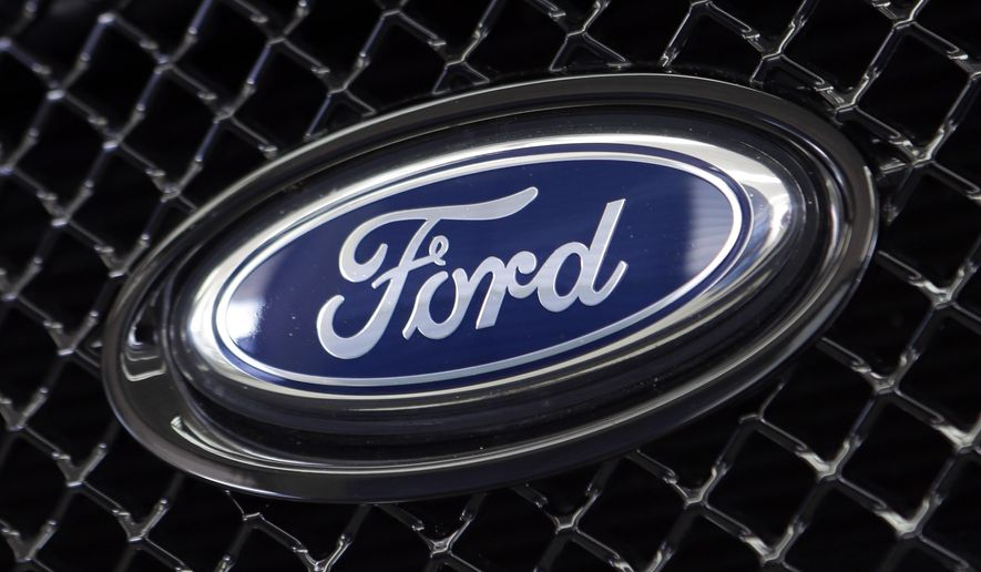 FILE - This Aug. 21, 2014 file photo shows the Ford logo on a vehicle at a dealership in Hialeah, Fla.  The U.S. government is investigating complaints that steering wheels can come loose on some Ford Fusion sedans. The National Highway Traffic Safety Administration says one driver complained that the wheel completely detached from the steering column. The probe revealed Friday, Oct. 27, 2017 covers about 841,000 midsize sedans from the 2014 through 2016 model years.(AP Photo/Alan Diaz)
