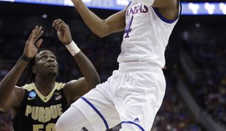FILE - In this Thursday, March 23, 2017, file photo, Kansas guard Devonte Graham (4) drives to the basket in front of Purdue forward Caleb Swanigan during the first half of a regional semifinal of the NCAA men's college basketball tournament, in Kansas City, Mo. Veterans such as Graham and Lagerald Vick should combine with newcomer Malik Newman and freshman Billy Preston to form a 2017-18 Kansas team that is once again favored to win the league. (AP Photo/Charlie Riedel, File)