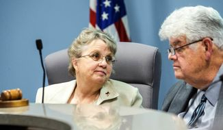 In this 2015 photo Arizona state schools Chief Diane Douglas looks to then president of the Arizona Board of Education Greg Miller in Phoenix. Miller, who resigned his post last year amid an ongoing battle with Douglas died Tuesday, Oct. 24, 2017, of natural causes after battling coronary artery disease for years. He was 69. (Nick Oza /The Arizona Republic via AP)