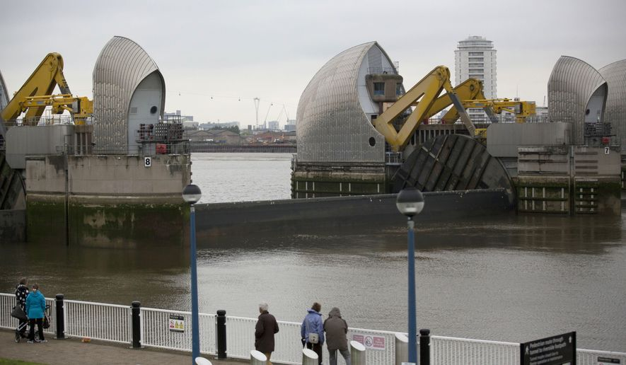 FILE - This Thursday, May 8, 2014 file photo shows a sector gate on the Thames Barrier reopening for one of its monthly tests on the River Thames in east London. It is designed to block exceptionally high tides or storm surges from the North Sea. (AP Photo/Matt Dunham, File)