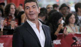 "FILE - In this file photo dated Wednesday, Sept. 14, 2011, Simon Cowell, executive producer and a judge on ""The X Factor,"" poses at a world premiere screening event for the new television series, in Los Angeles, USA.  According to a British national newspaper report Friday Oct. 27, 2017, entertainment mogul Simon Cowell has been hospitalized after a fall at his London home. (AP Photo/Chris Pizzello, FILE)"