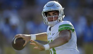 FILE - In this Oct. 21, 2017, file photo, Oregon quarterback Braxton Burmeister gets set to pass during the second half of an NCAA college football game against UCLA in Pasadena, Calif. With starting quarterback Justin Herbert out with a fractured collarbone, the Ducks have turned to true freshman Burmeister, who has had to learn on the job. (AP Photo/Mark J. Terrill, File)