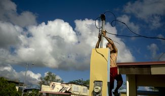 In this Friday, Oct. 13, 2017 file photo, a resident tries to connect electrical lines downed by Hurricane Maria in preparation for when electricity is restored in Toa Baja, Puerto Rico.  (AP Photo/Ramon Espinosa) **FILE**