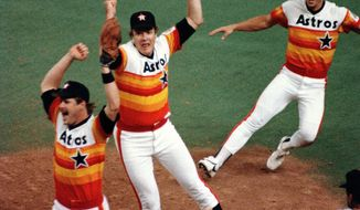 FILE - In this Sept. 25, 1986, file photo, Houston Astros pitcher Mike Scott, center, reacts at first base after pitching a no-hitter and winning the NL West Division against the San Francisco Giants in the Houston Astrodome in Houston, Texas. At left is first baseman Glenn Davis and at right is Bill Doran.  Those rainbow jerseys that were mocked so much when the Houston Astros debuted them decades ago have now become fan favorites at Minute Maid Park. The brightly colored style is sure to seen throughout the crowd when the World Series resumes this weekend. The Astros and Los Angeles Dodgers are all even going into Game 3.(AP Photo/Ed Kolenovsky, File)