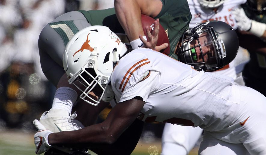 Texas defensive back Holton Hill (5) upends Baylor quarterback Charlie Brewer in the first half of an NCAA college football game, Saturday, Oct. 28, 2017, in Waco, Texas. (AP Photo/Rod Aydelotte)