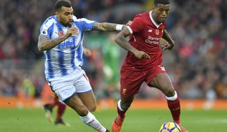 Huddersfield Town's Danny Williams, left, chases after Liverpool's Georginio Wijnaldum during their English Premier League soccer match at Anfield in Liverpool, England, Saturday Oct. 28, 2017. (Dave Howarth/PA via AP)