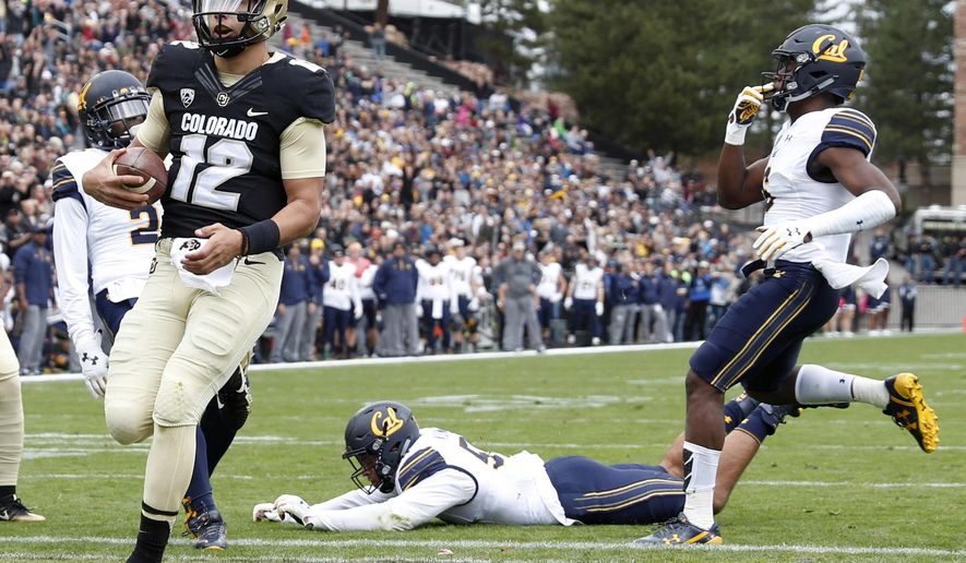 Colorado quarterback Steven Montez, front, runs past California defenders to score a touchdown in the first half of an NCAA college football game Saturday, Oct. 28, 2017, in Boulder, Colo. (AP Photo/David Zalubowski)