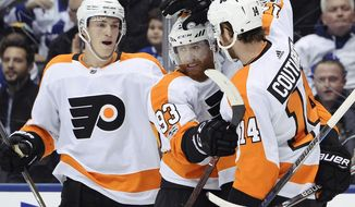 Philadelphia Flyers right wing Jakub Voracek, center, celebrates his goal against the Toronto Maple Leafs with teammates defenseman Travis Sanheim, left, and centre Sean Couturier during the first period of an NHL hockey game in Toronto on Saturday, Oct. 28, 2017. (Nathan Denette/The Canadian Press via AP)